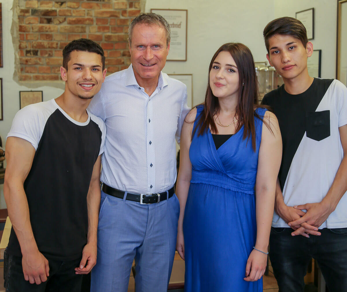 Friseurmeister Daniel Schmid mit den neuen Azubis: Stojan Siscovic, Polymnia Ioannidis und Hassan Rezai